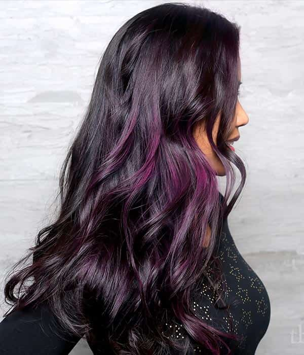 Profile of woman with dark almost black hair and purple pieces blended in.